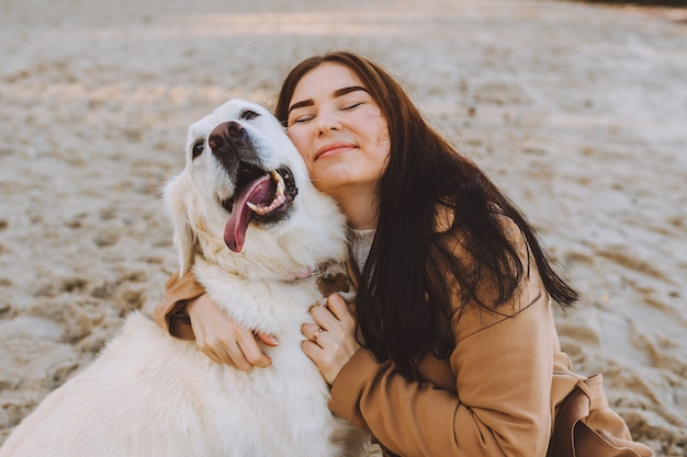 가 따뜻한 날에 해변에서 그녀의 황금 retreiver 강아지와 포옹하는 아름 다운 젊은 여자.