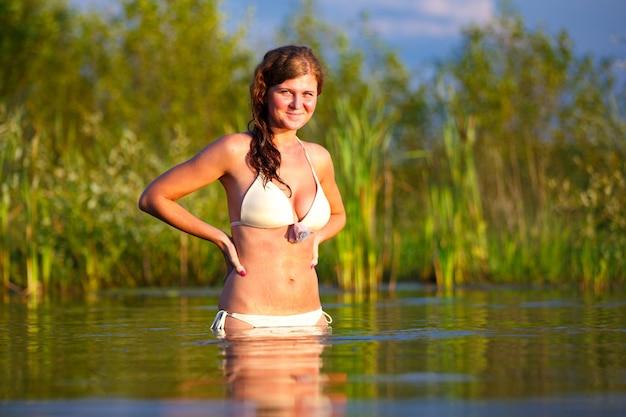 湖で水浴びをしているビキニの美しい若い女性。