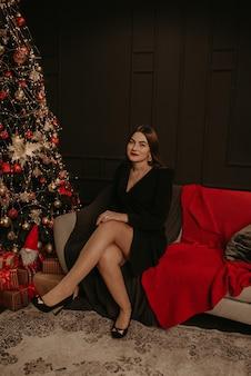 Красивая молодая женщина в черном платье возле елки в гирлянде