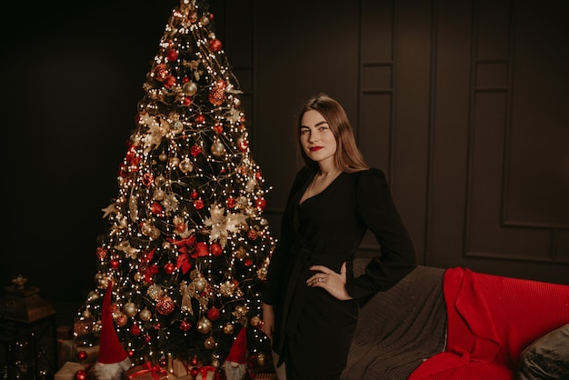 Красивая молодая женщина в черном платье возле елки в гирляндах.
