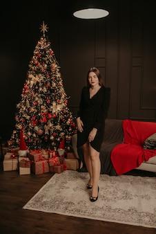 Красивая молодая женщина в черном платье возле елки в гирляндах