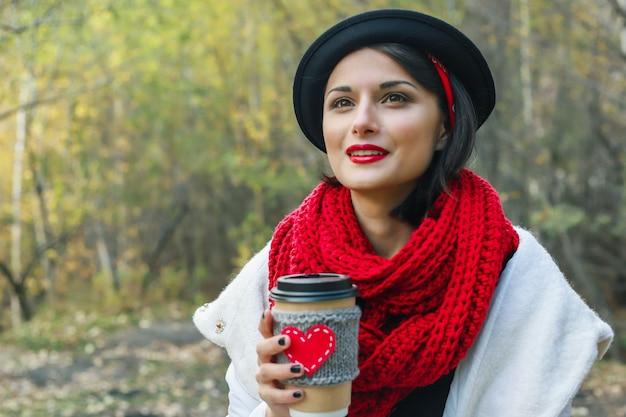 검은 모자를 쓴 아름다운 젊은 여성이 야외 피크닉 분위기에서 아늑한 컵으로 커피를 마신다