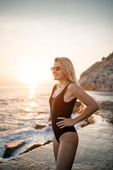 Красивая молодая женщина в черном купальнике одна на пляже у моря на закате. взрослая стройная девушка отдыхает на берегу океана на закате. концепция летних каникул. выборочный фокус
