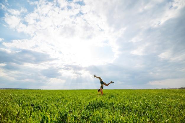 검은색 상의와 반바지를 입은 아름다운 젊은 여성이 물구나무서기를 수행합니다. 모델이 손에 서서 푸른 하늘을 배경으로 체조 스플릿을 하고 있습니다. 건강한 라이프 스타일 개념