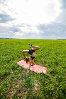 Красивая молодая женщина в черном топе и шортах выполняет стойку на руках. модель стоит на руках, делает гимнастический шпагат на фоне голубого неба. концепция здорового образа жизни
