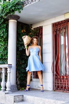 Красивая молодая женщина в синем платье позирует возле колонны