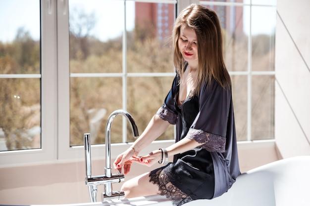Красивая молодая женщина в синем халате собирается принять ванну в солнечной ванной комнате