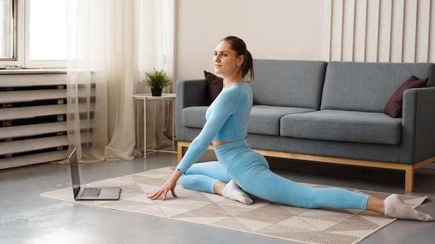 自宅でフィットネス運動をしている青いスーツを着た美しい若い女性。彼女は自分のラップトップを見て、オンラインコースの動きを繰り返します。