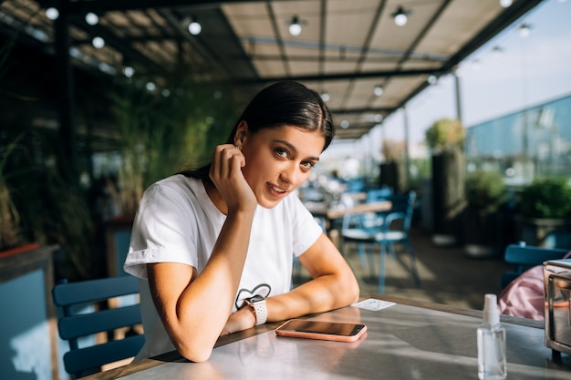 그녀의 손에 스마트 폰을 들고 카페에서 아름 다운 젊은 여자
