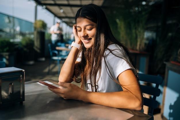 Красивая молодая женщина в кафе, держа в руках смартфон