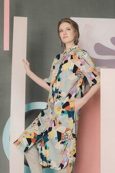 カラフルなインスタレーションの前でポーズをとるカラー ブロック ドレスを着た美しい若い女性