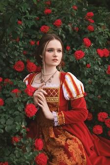 中世風のドレスを着た美しい若い女性が赤いバラと庭に座っています