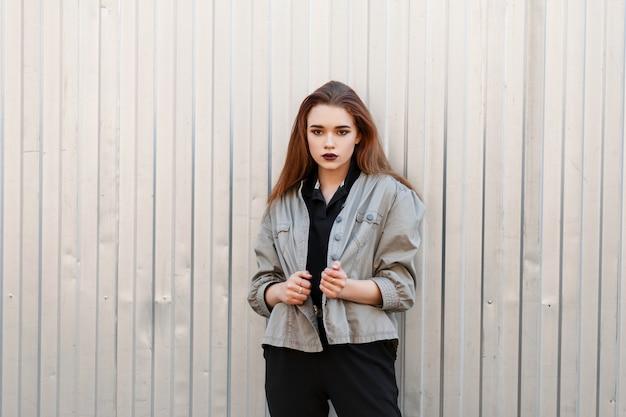 유행 재킷과 검은 셔츠에 아름 다운 젊은 여자는 거리에 금속 벽 근처에 서있다