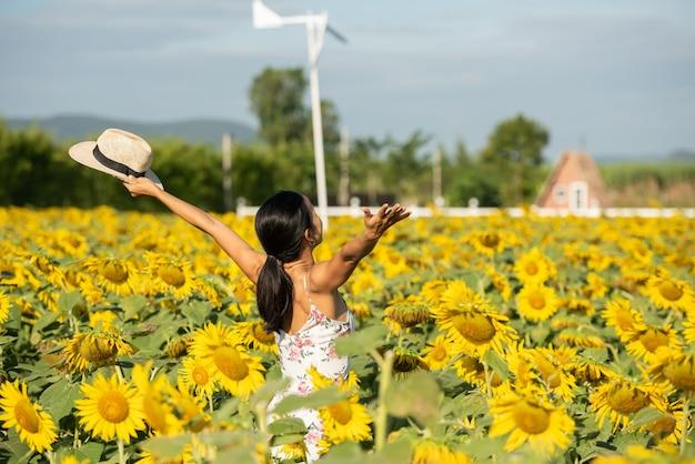 白いドレスを着たひまわり畑の美しい若い女性。週末のコンセプトで旅行します。麦わら帽子をかぶった本格的な女性のポートレート。ひまわり畑の野外。