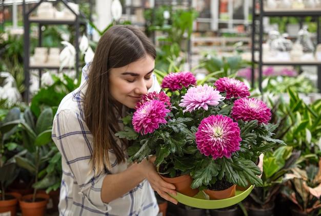 フラワーショップで花を選ぶ美しい若い女性。