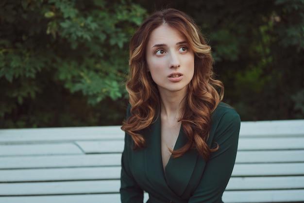 茂みの公園のベンチに緑のドレスを着た美しい若い女性