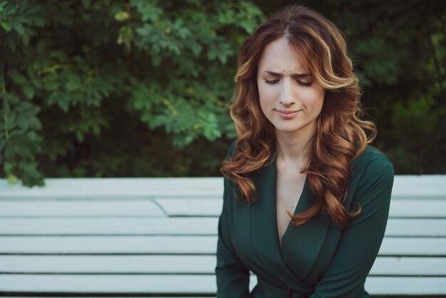 공원 벤치에 녹색 드레스에 아름 다운 젊은 여자