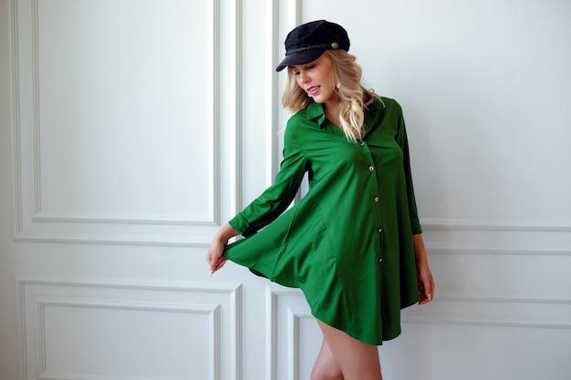 白い部屋でポーズをとって緑のショートドレスの美しい若い女性。ファッション、美容、魅力のコンセプト。