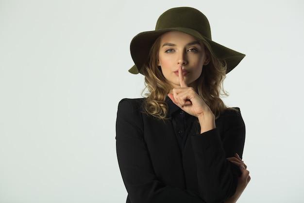 Красивая молодая женщина в шляпе на белой стене жестом руки означает тишину