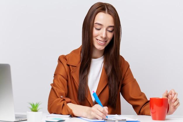 デスクのオフィスで働くジャケットの美しい若い女性