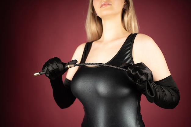 Красивая молодая женщина в латексном платье позирует с шлепками в руках