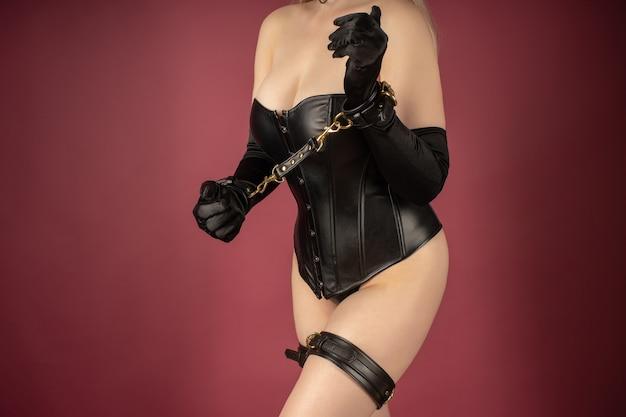 Красивая молодая женщина в кожаном корсете и бондаже позирует