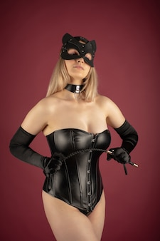 Красивая молодая женщина в кожаном корсете и маске кошки позирует с кнутом в руках