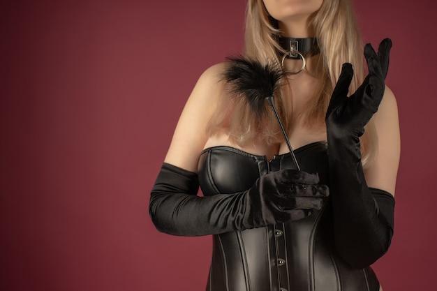 Красивая молодая женщина в кожаном корсете позирует с фетишем из перьев для ласки в руках