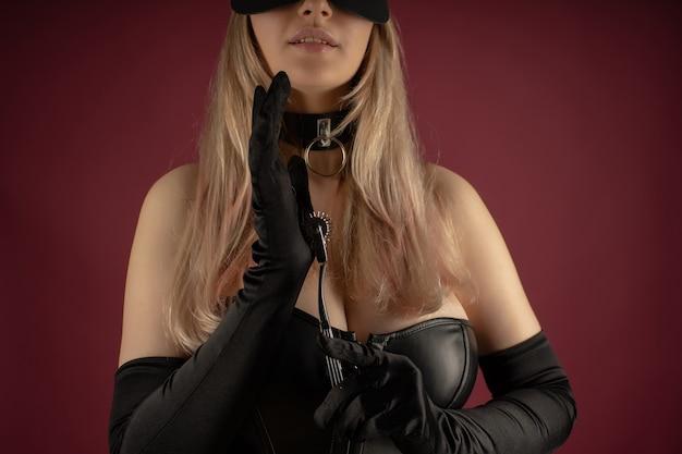 Красивая молодая женщина в кожаном корсете позирует с неврологическим фетишем с шипами в руках