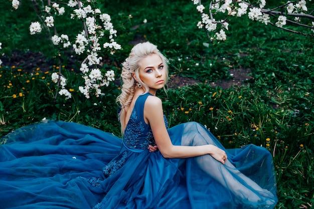 Красивая молодая женщина в длинном вечернем синем платье.