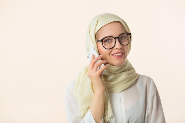 휴대 전화와 함께 흰색 배경에 이슬람 headscarf에서 아름 다운 젊은 여자