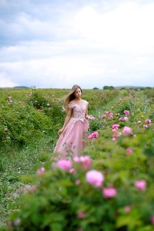 Красивая молодая женщина в розовом платье с длинными вьющимися волосами позирует возле роз в саду.