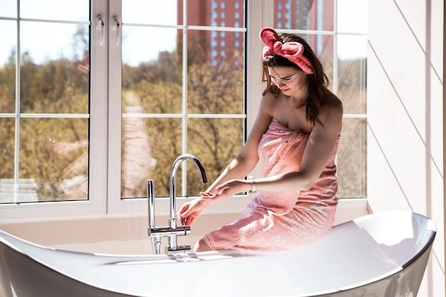 Красивая молодая женщина в розовом полотенце и с косметической повязкой на голове собирается принять ванну