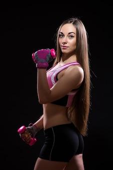 Красивая молодая женщина в красных боксерских перчатках, изолированные на черном фоне