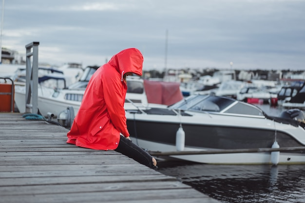 ヨット港の赤いマントの美しい若い女性。スウェーデンのストックホルム