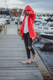 Beautiful young woman in a red cloak in the yacht port. Stockholm, Sweden
