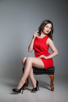 彼女の首に香水をスプレーする赤いドレスを着た美しい若い女性