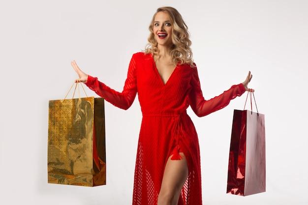 흰색 배경에 그들의 손에 패키지와 빨간 드레스에서 아름 다운 젊은 여자