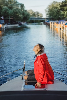 Beautiful young woman in a red raincoat rides a private yacht. Stockholm, Sweden