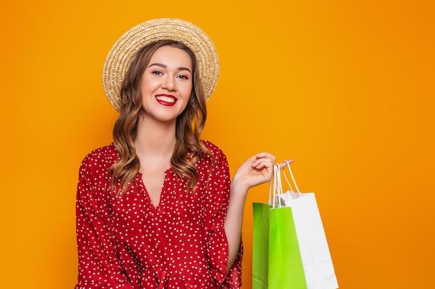 빨간 여름 드레스 밀 짚 모자에 아름 다운 젊은 여자는 오렌지 벽에 고립 된 그녀의 손에 쇼핑백을 보유하고있다. 쇼핑 선물 소녀는 카메라에 보이는