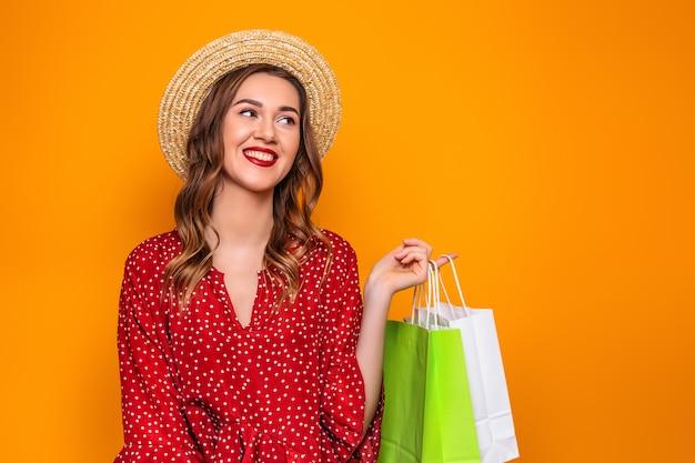 빨간 여름 드레스 밀 짚 모자에 아름 다운 젊은 여자는 오렌지 벽에 고립 된 그녀의 손에 쇼핑백을 보유하고있다. 여자 쇼핑 선물 본다