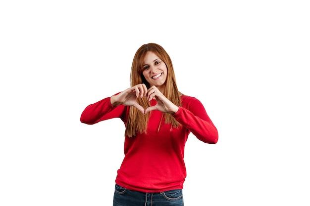 白い背景で隔離の彼女の手でハートのジェスチャーを作る赤いセーターを着た美しい若い女性。