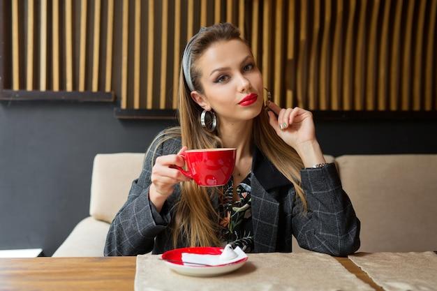 Красивая молодая женщина в ресторане с чашкой кофе