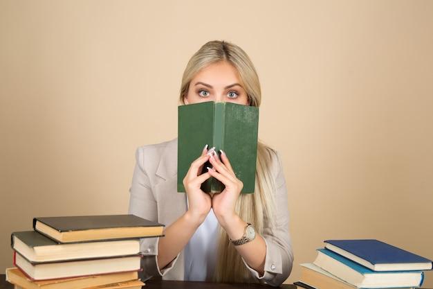 Красивая молодая женщина в костюме сидит за столом с книгами с удивленным лицом