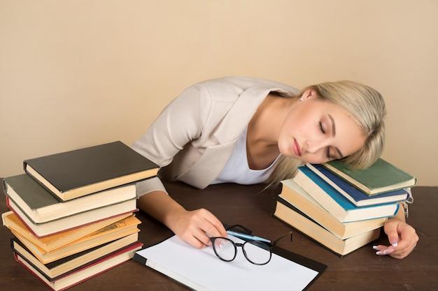 スーツを着た美しい若い女性が本とテーブルで寝る