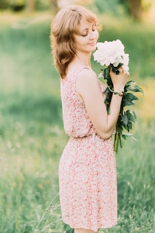 Красивая молодая женщина в летнем платье с пионами