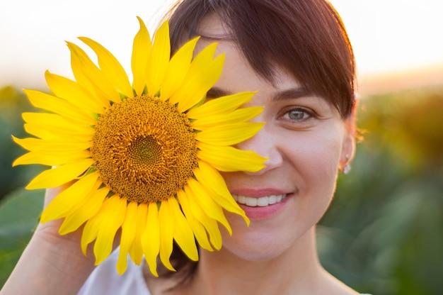 Красивая молодая женщина в поле подсолнечника. портрет молодой женщины на солнце. концепция аллергии на пыльцу. счастье на природе