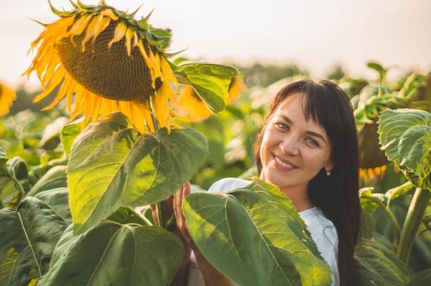 ひまわり畑で美しい若い女性。太陽の下で若い女性の肖像画。花粉アレルギーのコンセプト