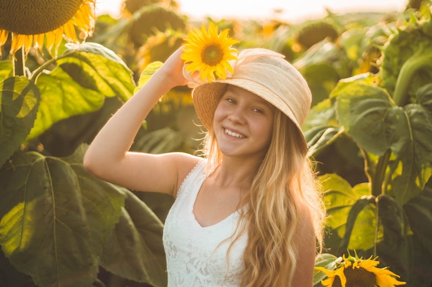 Красивая молодая женщина в поле подсолнечника. портрет молодой женщины на солнце. концепция аллергии на пыльцу