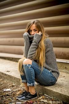 通りに座っている長い髪のセーターの美しい若い女性